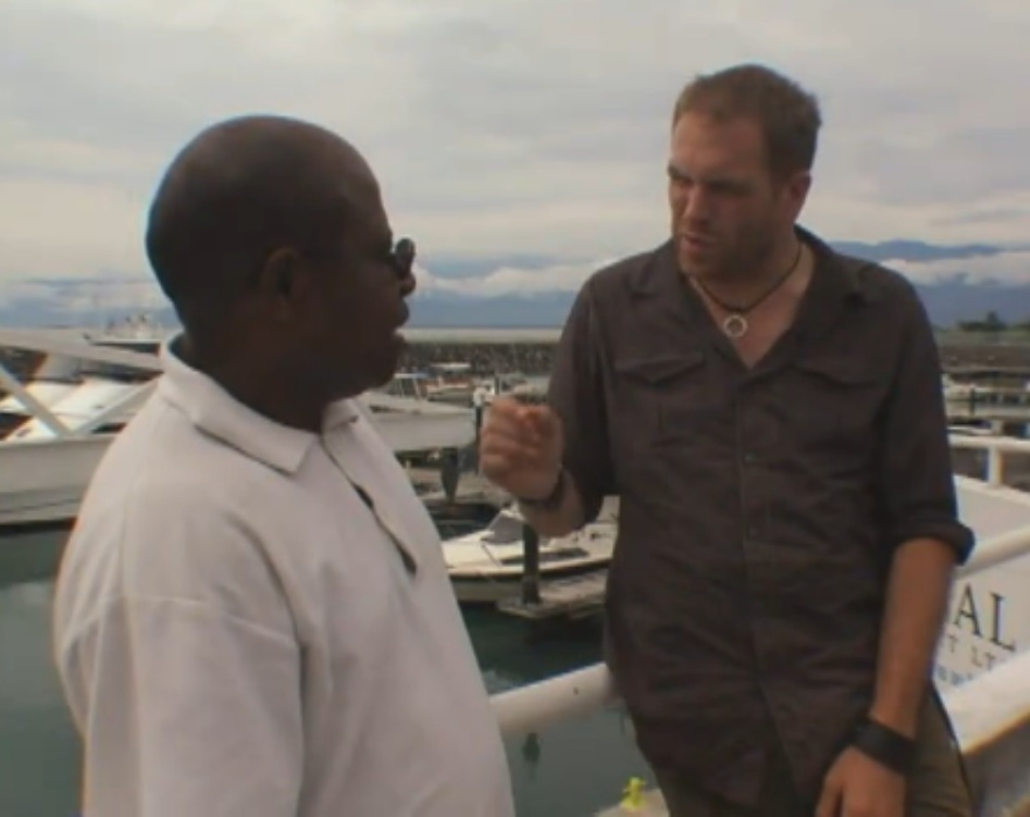 At a harbor in Papua New Guinea, native interpreter Jacob Kepas is interviewed by the American Josh Gates