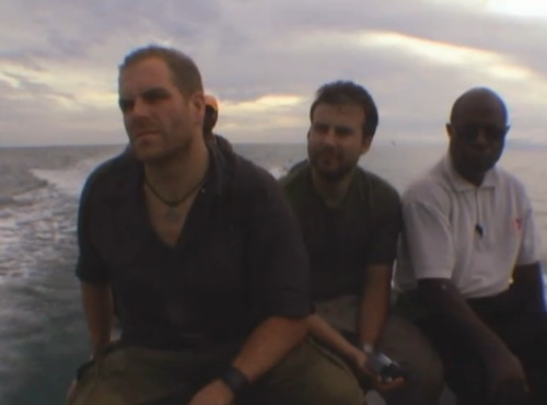 Three expedition-team members on a small boat in Papua New Guinea